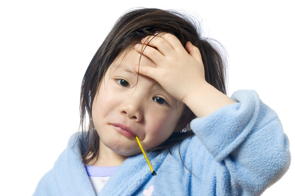 A young girl is sick and having her temperature taken; blog: common childhood illnesses