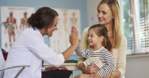 mom with daughter sitting in lap giving pediatrician high five; blog: 5 Reasons Well Child Visits are Important