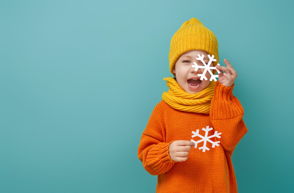 Winter portrait of happy child wearing knitted hat, snood and sweater. Girl having fun, playing and laughing on teal background; blog: Cold Weather Activities