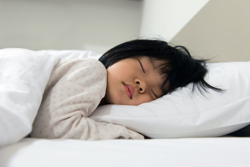 Portrait of Asian child sleeping on the bed; blog: Healthy Sleep Routines Tips and Tricks